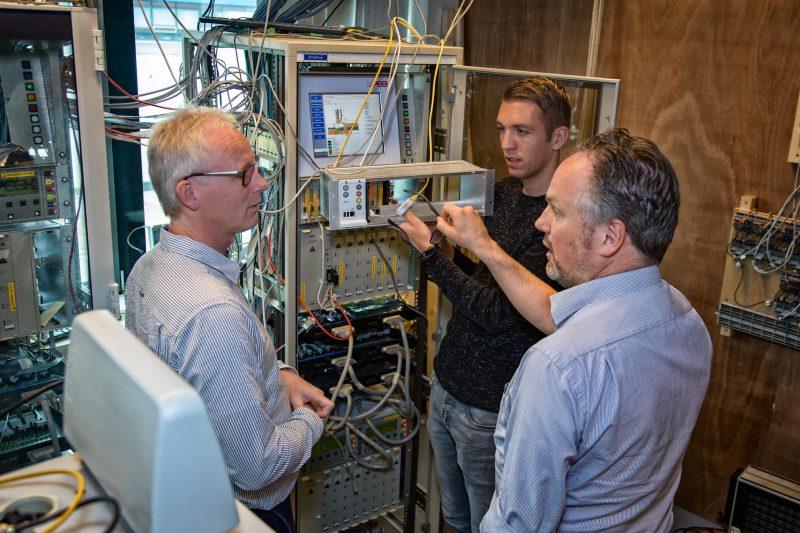 Igor Passchier van Tass International (L) in gesprek met Pascal de Jong en Peter Bouwens (R) van Dynniq bij een testmodel van de iVRI